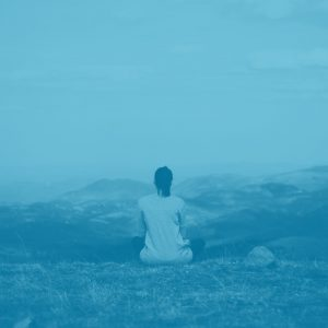 duotoned blue image of woman sitting on a cliff, shot from behind her