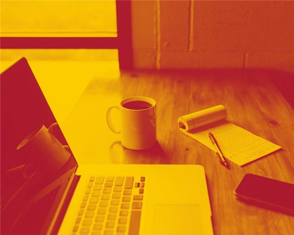 yellow duotone desk with laptop, mug of coffee and notepad and pen